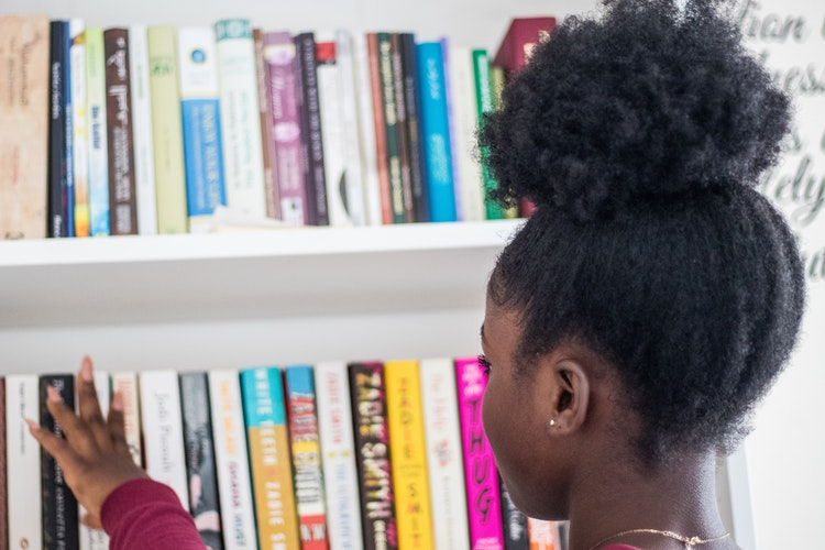6 Must-Read Books to Celebrate Black History Month: Young Lady Standing in Front of a Bookshelf