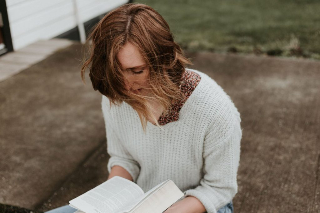Image of girl reading book outside: 13 New Fiction Releases for Character-Driven Readers